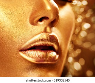 Fashion art Golden skin Woman face portrait closeup. Beauty gold Lips and Skin. Model girl. Glamour shiny professional makeup