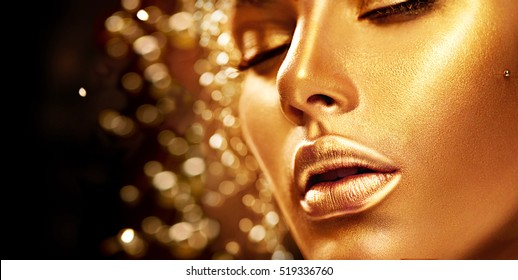 Fashion art Golden skin Woman face portrait closeup. Beauty gold eyes, Lips and Skin. Model girl. Glamour shiny professional makeup