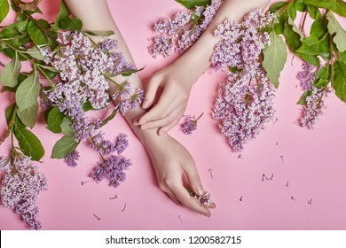 Fashion art hands natural cosmetics women, bright purple lilac flowers in hand with bright contrast makeup, hand care. Creative beauty photo of a girl sitting at table on contrasting pink background