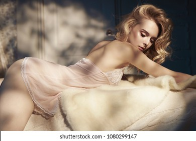 Fashion art photo of beautiful sensual woman in pink negligee in her boudoir. Home bedroom interior. Beautiful morning. Summer sunset