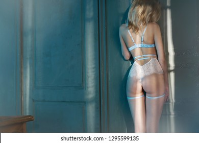Fashion art photo of beautiful sensual woman in sexy lingerie. Home interior. Beautiful morning light in the dark room. Pretty lady with perfect body pose in hotel.