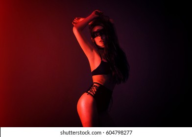 Fashion art photo of elegant model in seductive black lingerie and mask with light red neon colored club spotlights
