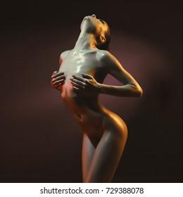 fashion art photo of elegant nude model in the light colored spotlights