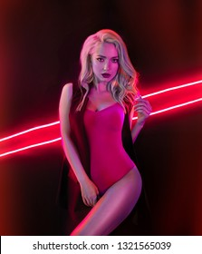 Fashion art photo of elegant sexy girl model in seductive red swimsuit with light neon colored club spotlights Night club sexy concept