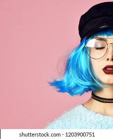 Fashion art photo of young grunge style woman with blue wig hair in gold chain choker on neck and black leather hat on pink background