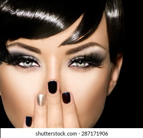 Fashion Art Portrait Of Beautiful Girl. Vogue Style Woman. Hairstyle. Black Hair and Nails. Isolated on Black Background. Beauty Stylish Model Portrait. Fringe haircut, hairstyle