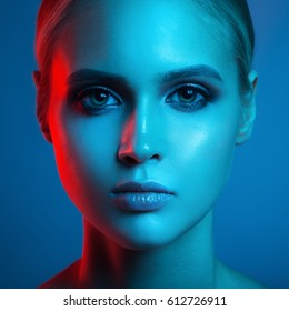 Fashion art portrait of beautiful woman face. Red and blue light color.