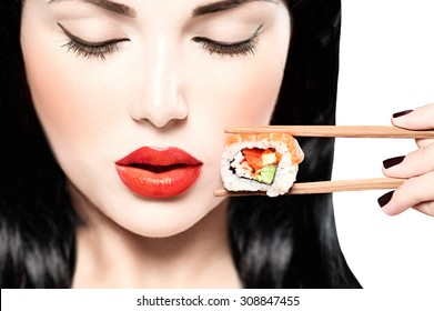 Fashion art portrait of beauty model girl eating Sushi roll, healthy japanese food. Beautiful woman holding chopsticks with sushi. Sexy lady
