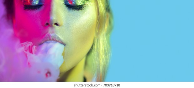 Fashion art portrait of beauty model woman in bright lights with colorful smoke. Smoking girl, Close up of a female inhaling from an electronic cigarette. Night life concept