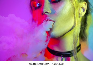 Fashion art portrait of beauty model woman in bright lights with colorful smoke. Smoking girl, Close up of a female inhaling from an electronic cigarette. Night life concept.