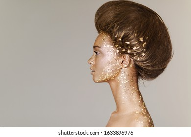 Fashion art portrait of model girl with holiday golden shiny professional makeup. woman with gold metallic body and hair on gray background. Gold glowing skin. copy space