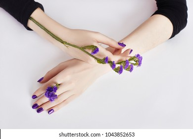 Fashion art skin care of hands and purple flowers in hands of women. Creative beauty photo hands, sitting at table on a contrasting pink background with colored shadows. Cosmetics for hands anti wrink