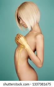Fashion art studio photo of elegant nude woman with golden body. Fashion and beauty. Conceptual image. Metallic art, body art. Slim, fit woman. Gold skin