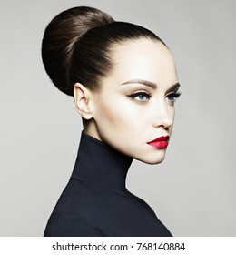 Fashion art studio portrait of beautiful elegant woman in black turtleneck.  Hair is collected in high beam.  Elegant ballet style