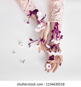 Fashion art woman in summer dress and flowers in her hand with a bright contrasting makeup. Creative beauty photo girls sitting at table on a contrasting pink background with colored shadows