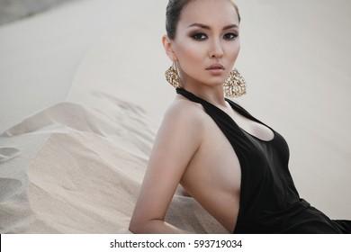Mode asian sexy Frau Modell posieren in Luxuskleid in der Wüste