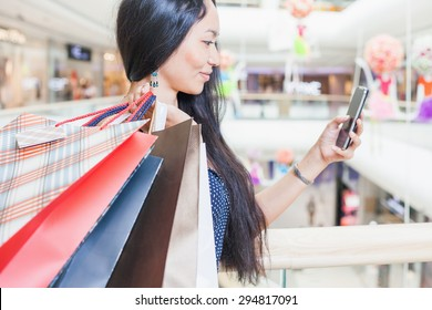 Fashion asian woman with a bag using mobile phone at big shopping center indoor. She received message about sale and discount! Concept of shopping or shopaholic, sales and discounts at boutique