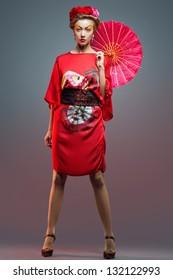 Fashion asian woman wearing traditional japanese red kimono  with umbrella, studio shot.  Geisha