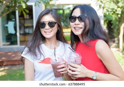 Fashion Asian women friendship wearing sunglasses and holding iced coffee at outdoor coffee cafe - young female best friends lifestyle portrait