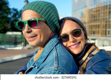 Fashion autumn close up Portrait of loving senior couple.Cute couple hugging in the park on a sunny day.Pretty couple hugging and flirting in an urban park,wearing headwear,jeans coat and sunglasses