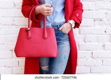 Fashion autumn outfit woman posing in red coat with leather bag near white wall . Stylish trendy accessory