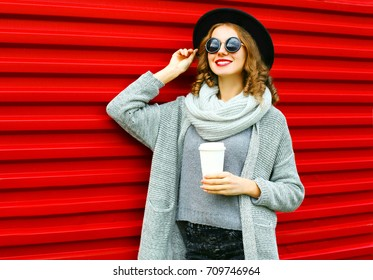 Fashion autumn portrait smiling woman with coffee cup is wearing a knitted clothes on a red background