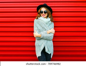 Fashion autumn portrait smiling woman wearing a knitted clothes on a red background