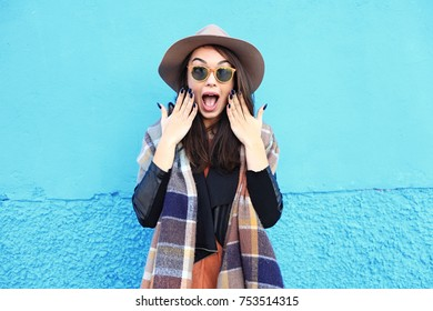 Fashion autumn portrait woman in trendy hat on a blue background