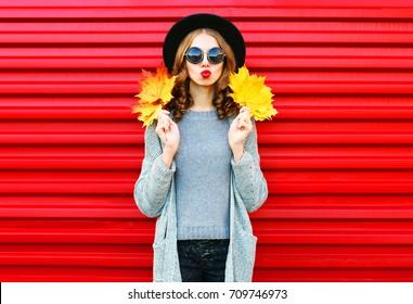 Modeherbstporträt mit gelben Ahornblättern auf rotem Hintergrund