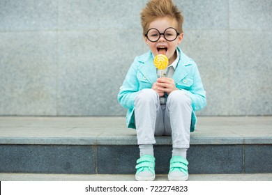 Fashion baby boy in mint jacket and sneakers stands on a gray wall background. Trendy boy with lollipop standing on the street.