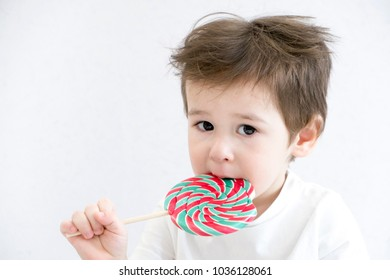 Fashion baby boy. Trendy boy with lollipop. funny cute little infant in white t-shirt.