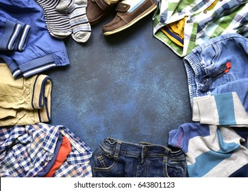 Fashion background with set of baby clothes on a dark blue slate,stone or concrete backdrop.Top view with copy space.