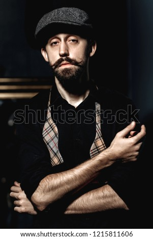 Fashion barber with mustache and beard in a flat cap and black shirt with  untied bow 3cd5188bc37
