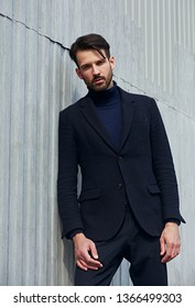 Fashion beard style business handsome male model posing in style clothing blue jacket and trousers on street wall outdoors background. Closeup portrait.