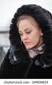Fashion beautiful blonde woman  in the black coat.