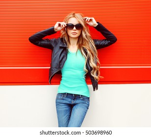 Fashion beautiful blonde woman model in sunglasses black rock jacket at city over red background