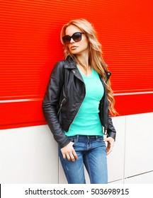 Fashion beautiful blonde woman in sunglasses black rock jacket at city over red background