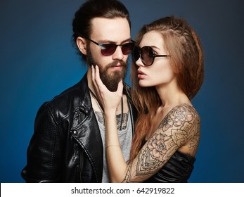 fashion beautiful couple in sunglasses.bearded Hipster boy and beauty girl in trendy glasses over blue background