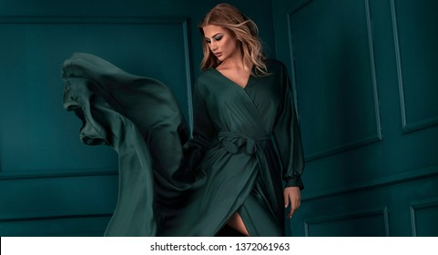 Fashion beautiful elegant woman posing in green maxi dress.
