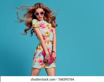 Fashion. Beautiful Lady in floral summer dress, long hair, makeup. Model girl with fashionable clutch bag on blue. Pretty blonde woman in fashion sunglasses, trendy hairstyle, summertime outfit