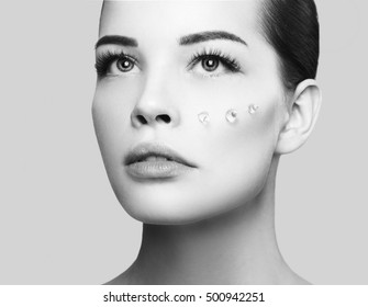 Fashion beautiful woman face with drops of gel on another cheek