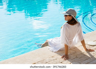 Fashion beautiful woman on summer vacation relaxing at luxury resort spa poolside. Young  fashionable lady wearing sun hat and white kaftan.