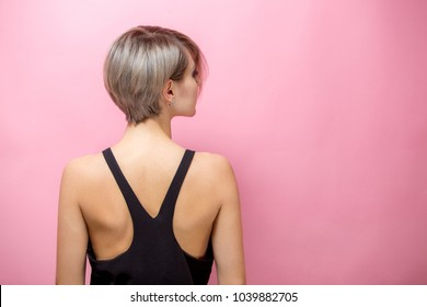 Fashion beautiful young woman with short hair over pink background. Back of beauitful  in black t- shirt