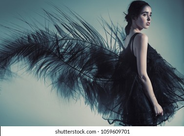 Fashion, beauty. Brunette woman in dress and black feather on the back
