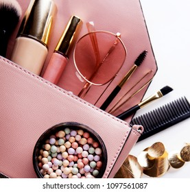 Fashion and beauty concept : Flat lay of pink leather woman bag open out with cosmetics and accessories on white background.