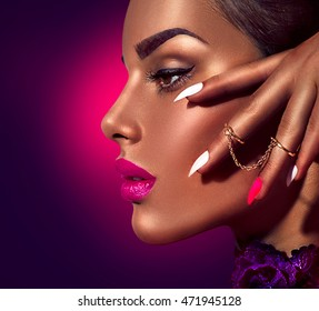 Fashion Beauty Girl. Gorgeous Woman profile Portrait. Stylish Makeup, manicure and accessories. Make up. Sexy Glamour lady face, model with brown skin and purple lips over dark background