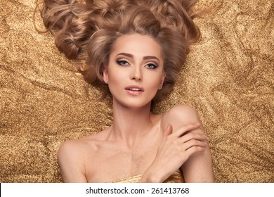 Fashion Beauty Girl Lying On Golden Glitter.
