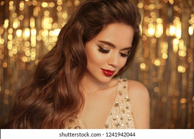 Fashion Beauty Girl Portrait Isolated on golden Christmas glittering bokeh lights background. Glamour Makeup. Gold Jewelry. Hairstyle. Alluring brunette with sensual red lipstick looking at camera.