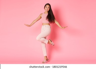 Fashion, beauty and lifestyle concept. Silly and glamour beautiful asian girl posing coquettish over pink background, smiling and raising foot, advertisement of women selfcare and shopping
