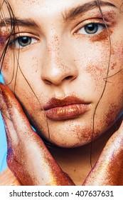 Fashion, beauty, make up, body art. Close up portrait of beautiful woman with orange glitters on face